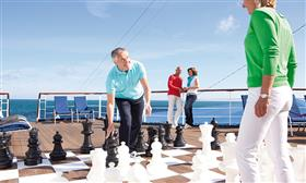 Two passengers playing with the giant chess board on-board Astor by Cruise&Maritime.
