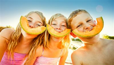 Happy kids wearing melon slices on their smiles