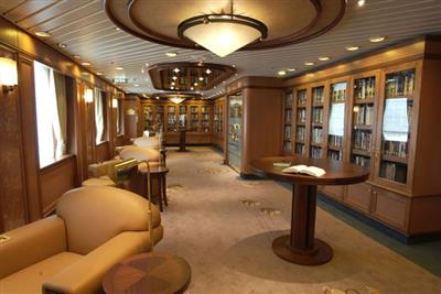 A comfy chair and round table  in the library onboard Crown Princess