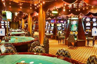 Green tables  and  slot machines  in  Costa Luminosa's casino
