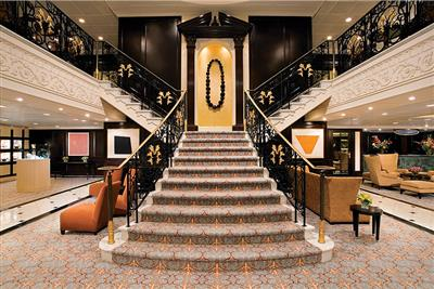 The graceful grand staircase in the atrium of the Azamara Quest.