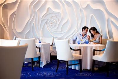 A couple having a romantic dinner in the main restaurant on board Celebrity Eclipse.