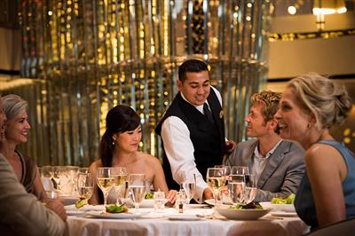 A waiter serving a delicious dinner onboard Celebrity Eclipse.