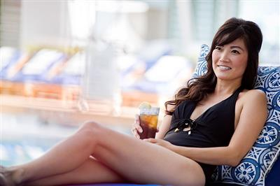 A smiley lady enjoying a cocktail  at the pool side on Celebrity Equinox.