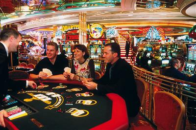 Passengers playing at the blackjack table in the casino on board of Adventure of the Seas.