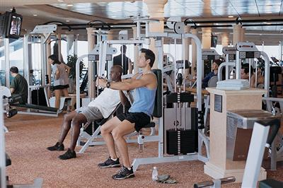 Cruisers sticking to their fitness routine at the fully equipped gym onboard Brilliance of the Seas.