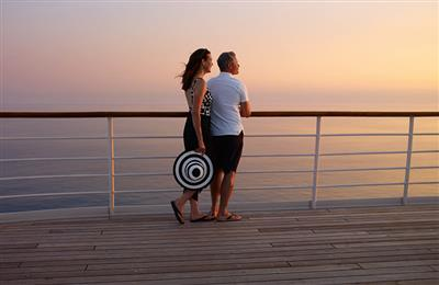 A couple leans on the external rail and enjoy the sunset