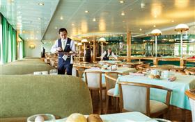 Two waiters setting up the breakfast tables on-board Astoria.