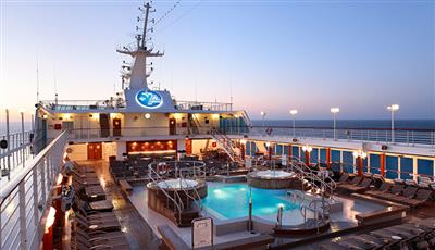 The sunset on the outdoor top deck pool of Azamara Quest.