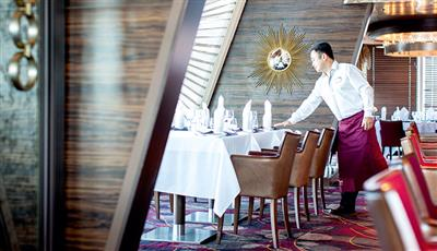 A waiter checks the table in the Surf and Turf Steakhouse on the Marella Discovery 2