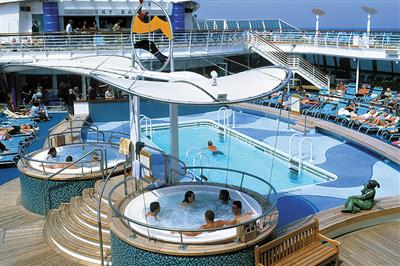 Customers enjoying the outdoor swimming pool and the whirlpool baths on board Brilliance of the Seas.