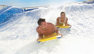 Two passengers  having fun on the adrenaline-pumping surf simulator on the Allure of the Seas.
