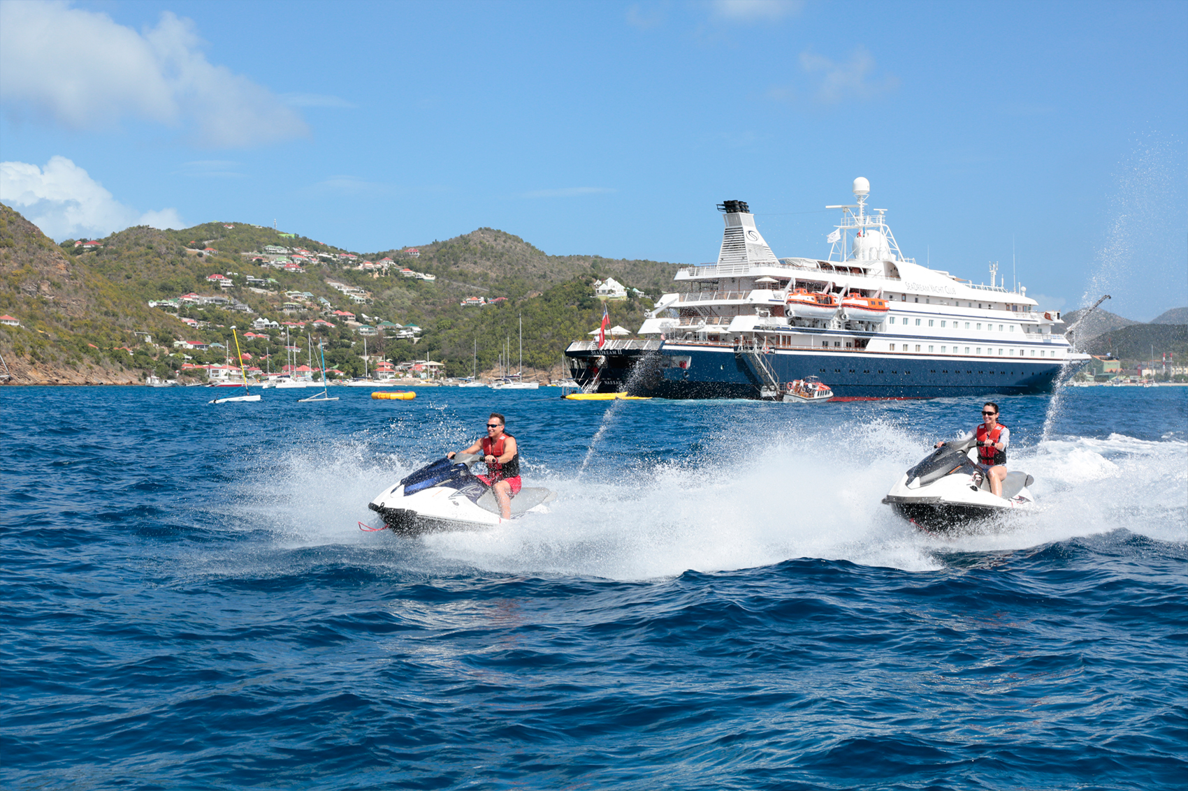 Cruisers riding jet skis wwith a SeaDream ship in the background
