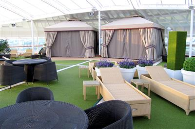Tables and sunbeds into the outdoor lounge area on P&O Azura.